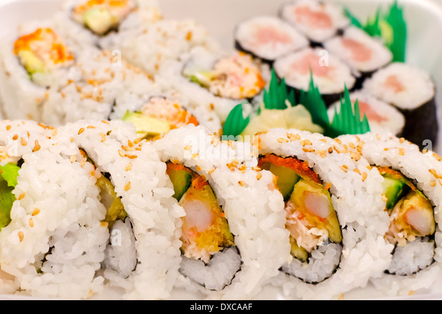 Take out or take away container of fresh sushi rolls - dynamite roll, tuna roll and California roll. - Stock Image