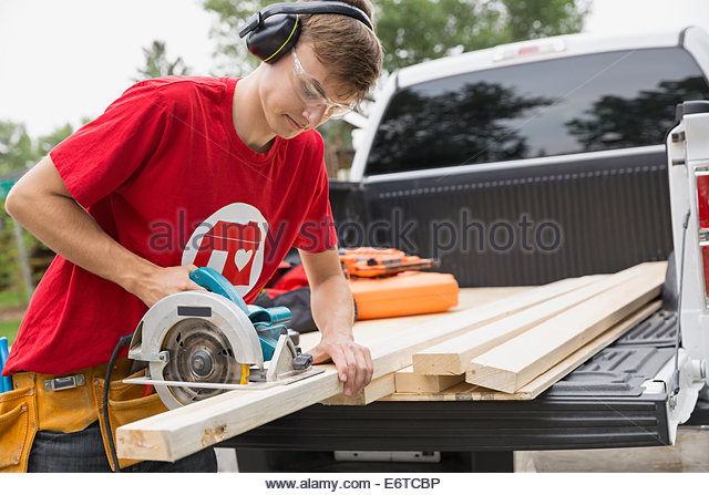 Volunteer using saw on wood on tailgate - Stock Image