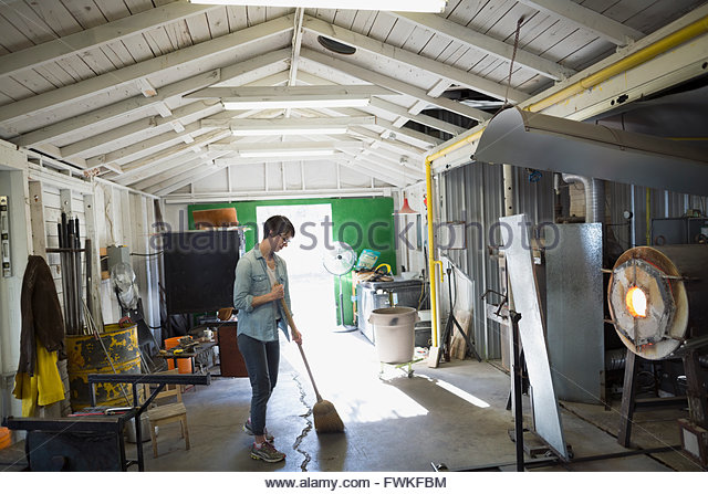 Female glassblower sweeping in workshop - Stock Image