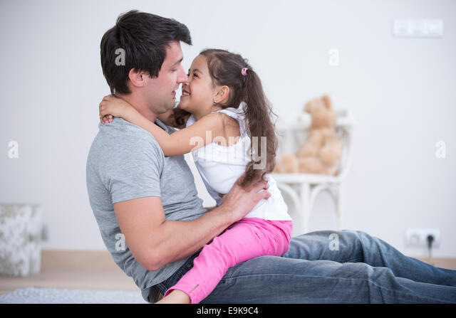 Side view of father and daughter spending quality time at home - Stock Image
