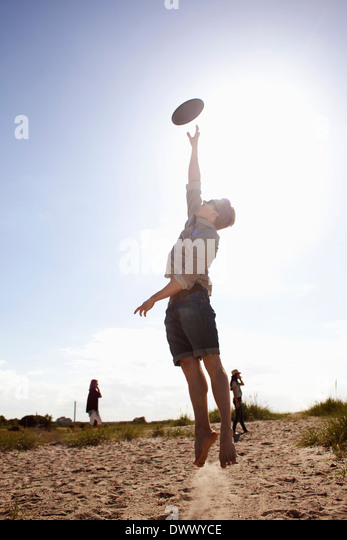 Young man in midair catching plastic disc - Stock Image