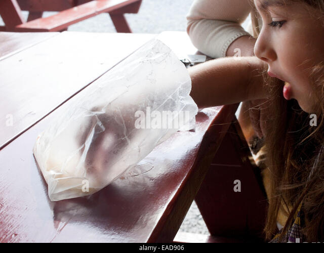 young girl reaching in empty bag of french fries - Stock Image