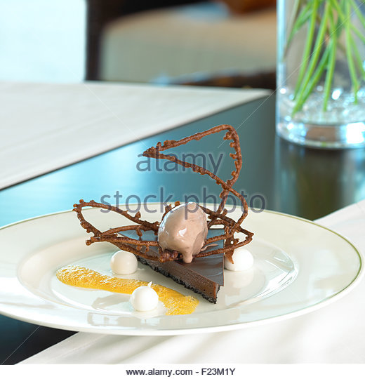Chocolate cheese cake with coffee ice cream chocolate pretzel and mango foam - Stock Image