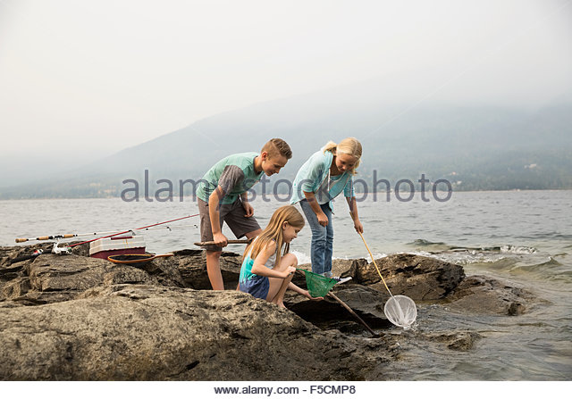 Brother and sisters fishing with nets craggy lakeside - Stock Image