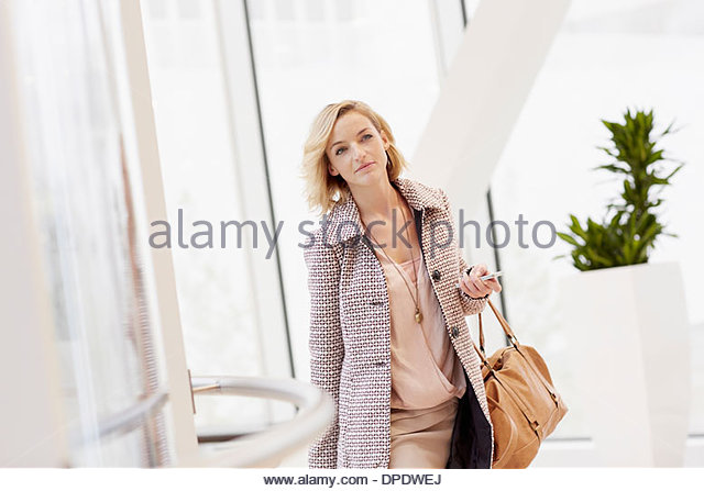 Mid adult woman with trolley case arriving at city airport - Stock Image