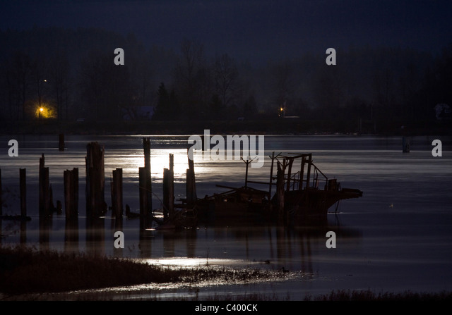 Full moon illuminates wreckage in the Pitt River, Port Coquitlam, BC, Canada - Stock Image