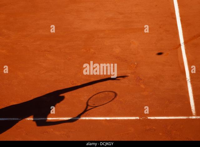 Shadow of a tennis player serving the ball. - Stock-Bilder