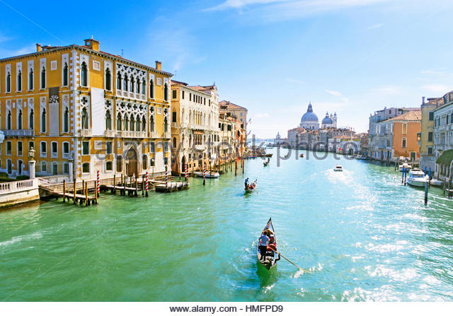 Gondoliers paddling tourists in gondola among architectural buildings in sunny Grand Canal in Venice, Italy - Stock-Bilder