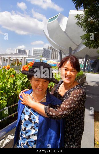 Singapore ArtScience Museum Asian woman mother adult daughter hugging smiling - Stock Image