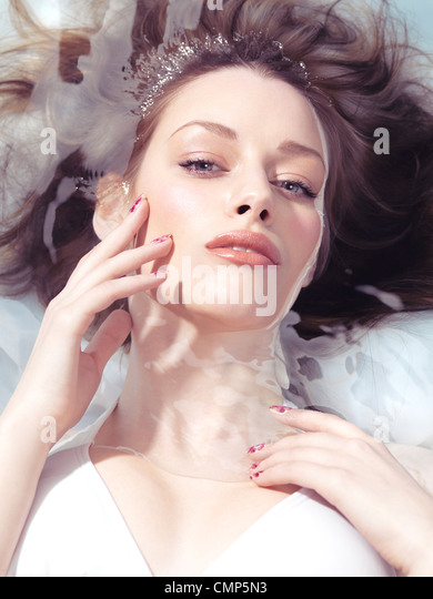 Beauty portrait of a young woman lying relaxed in water in bright sunlight. Beauty treatment concept. - Stock-Bilder