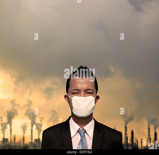 sad bussinessman with  mask and air pollution concept - Stock Image