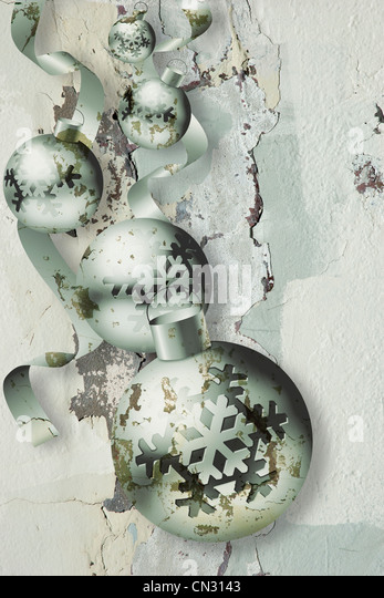 Christmas ball ornaments superimposed on textured peeling, decayed greenish gray wall background - Stock Image