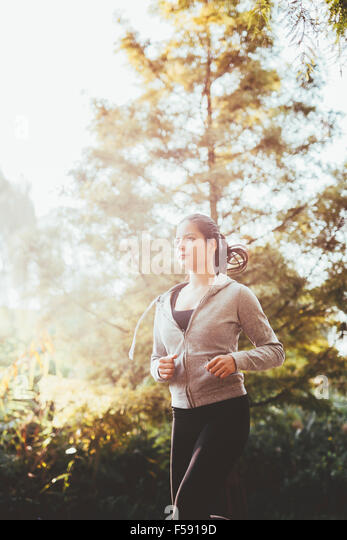 Fit woman jogging in park sorrounded by trees - Stock Image