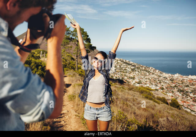Happy young woman posing with her arms raised to her boyfriend taking her photos with digital camera. Summer vacation - Stock Image
