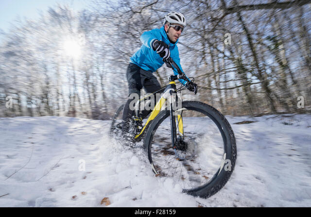 Mountain biker riding a bike in a snowy forest, Bavaria, Germany - Stock Image