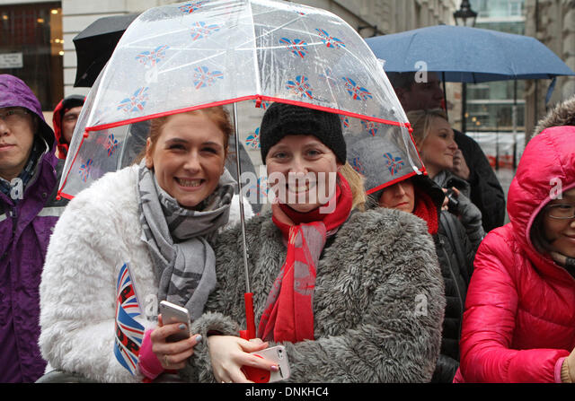 London,UK,1st January 2014,Sheltering under an umbrella at the London's New Year's Day Parade 2014 Credit: - Stock Image