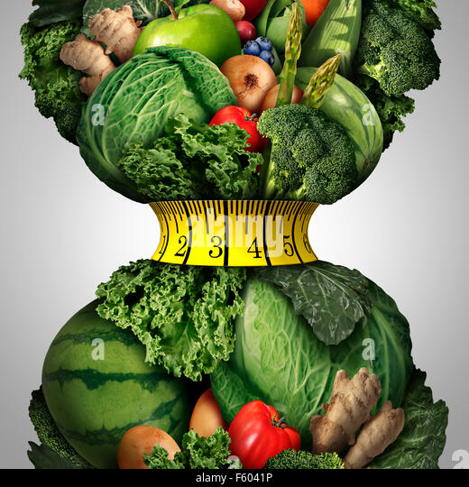 Healthy weight loss diet as a group of fresh fruits and vegetables with a fitness tape measure wrapped around a - Stock Image
