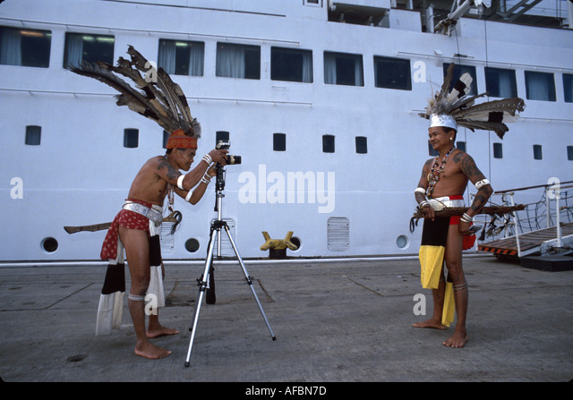 Malaysia Borneo Sarawak Kuching Iban tribesmen warriors by cruise ship looking at modern camera tripod - Stock Image