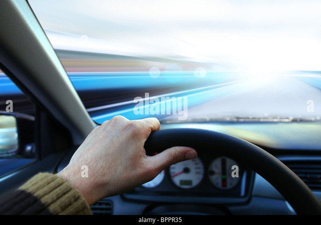 hand of driver that holds wheel and goes on road - Stock Image