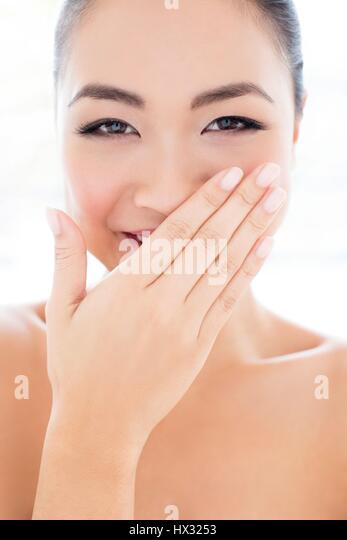 MODEL RELEASED. Young Asian woman laughing with hand covering mouth, portrait. - Stock-Bilder
