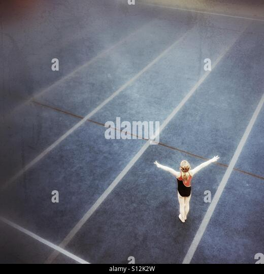 A young gymnast begins her floor routine. - Stock Image