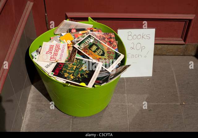 a plastic tub full of cheap second hand paperback books - 20p each, outside a uused bookshop UK - Stock Image