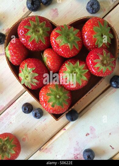 Fresh strawberries in love hearth shape basket and blueberries on vintage table in retro style background - Stock Image