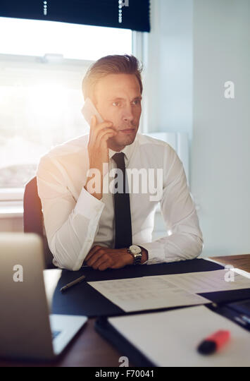 Business man having a conversation on the phone at his office - Stock Image