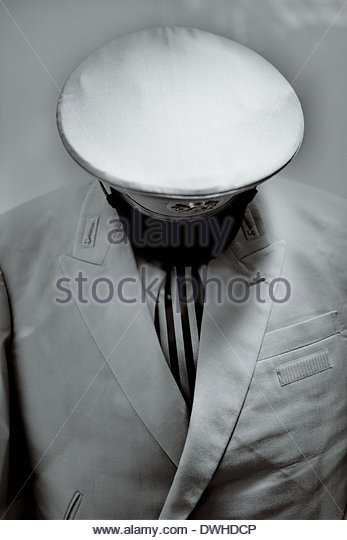 The peaked cap of railway conductor's uniform creates a surreal headless figure. - Stock Image