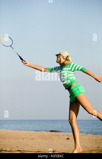Young woman playing badminton on beach - Stock Image