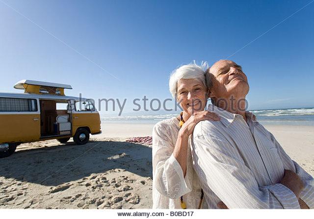 Senior woman embracing senior man from behind on beach by camper van, smiling, portrait - Stock-Bilder