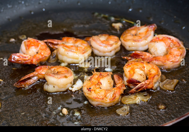 cooking shrimp in a pan in the kitchen at the restaurant - Stock Image