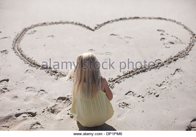 Girl drawing heart in sand on beach - Stock Image