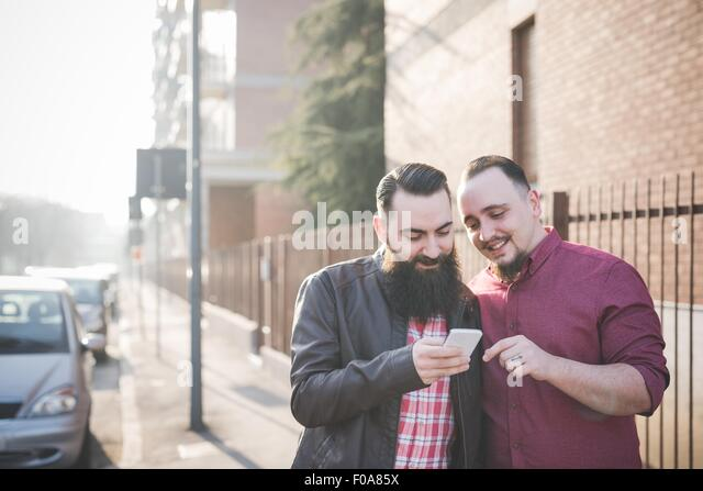 Gay couple using smartphone on pavement - Stock Image