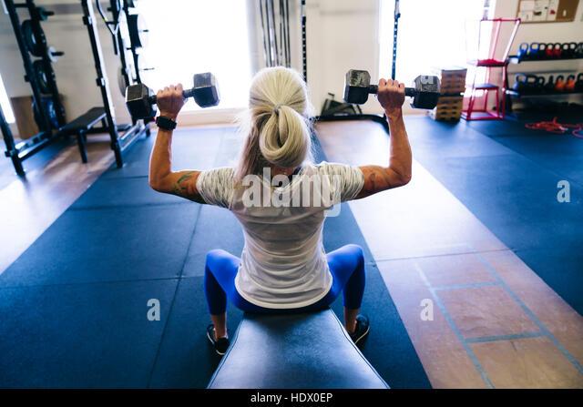 Caucasian woman lifting dumbbells in gymnasium - Stock Image