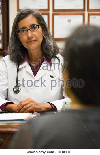 Mixed Race doctor talking to patient - Stock Image