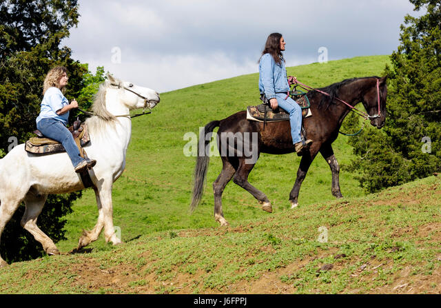Tennessee Sevierville Five Oaks Riding Stables horseback riding woman Native American man trail guide horse animal - Stock Image