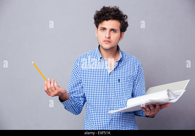 Young serious man holding pencil and folder with files over gray background. Looking at camera - Stock Image