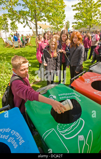 School children at the Hay festival putting waste containers in a bin for recycling. - Stock Image