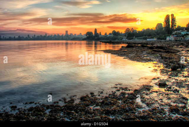 This vivid sunrise over Vancouver with the bay in the foreground is a beautiful landscape. - Stock Image