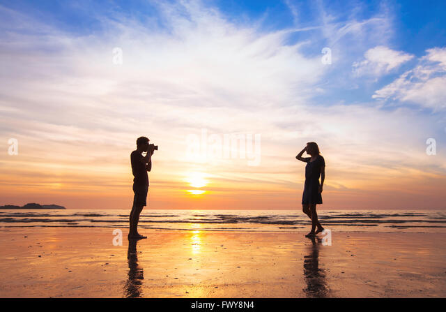 photographer and model, beach photo shooting at sunset, man taking pictures of woman - Stock Image