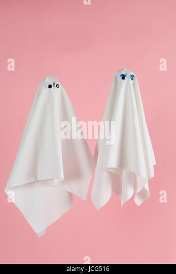 Couple of white sheet ghost with doll's eyes isolated on a pink background. Minimal pop still life photography - Stock Image