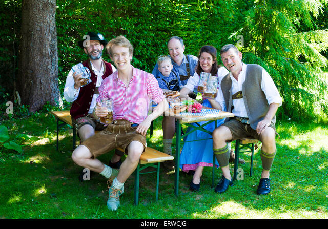 bavarian family sitting outside on a bench and drinking beer - Stock-Bilder