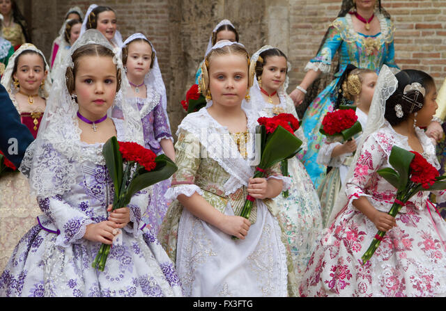 Children in traditional local costume attending the procession honouring the Lady of Valencia, Valencia Spain - Stock Image