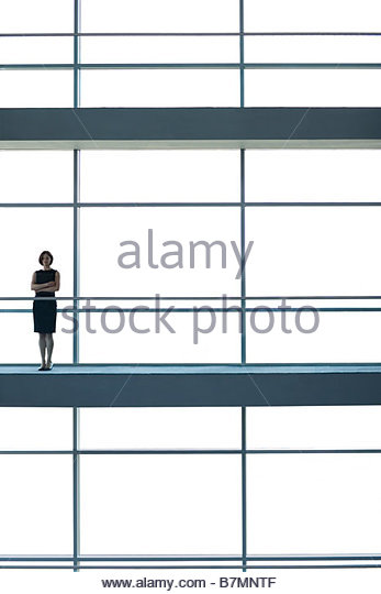A businesswoman standing on a walkway of large modern office building - Stock-Bilder