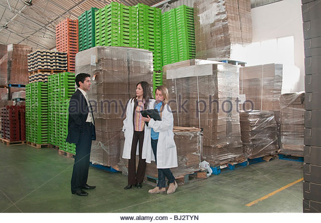 manager with workers in warehouse - Stock Image