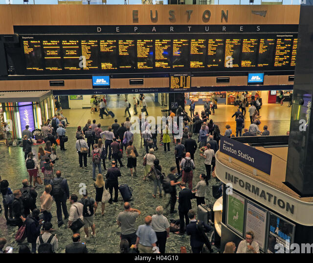 Euston railway station departure board and concourse, North London, England, UK - Stock Image