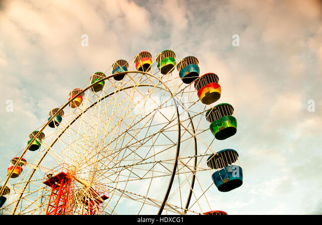 Colorful ferris wheel in sunset with cloudy sky - Stock Image