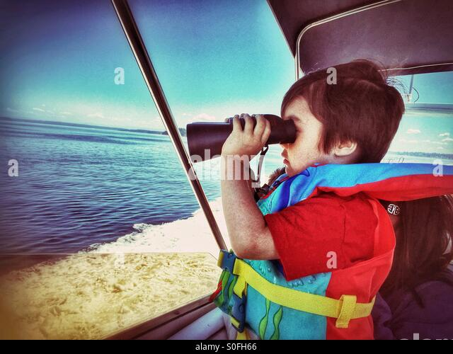 A little boy on a boat ride wearing a life jacket looks out to sea using a pair of binoculars. - Stock Image