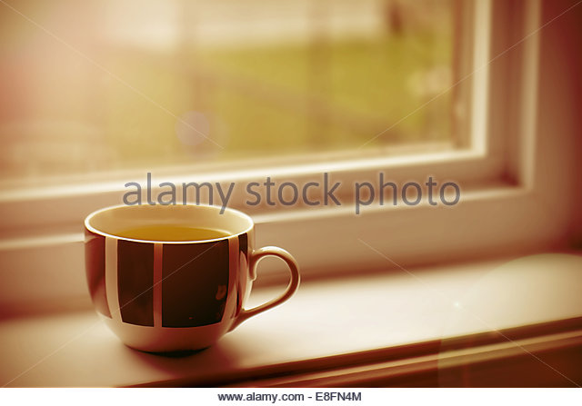 Cup on window sill - Stock Image